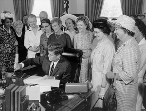 President John F. Kennedy signs the 1963 Equal Pay Act into law as BPW/USA president Dr. Minnie Miles watches.